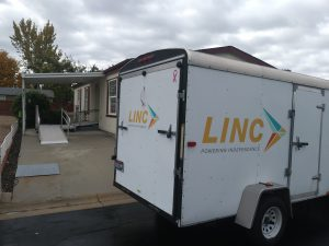 LINC equipment trailer in front of house with ramp