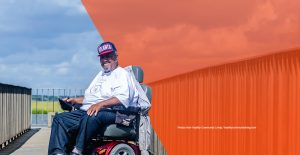 banner man using power wheelchair on a wooden walkway with orange border on right